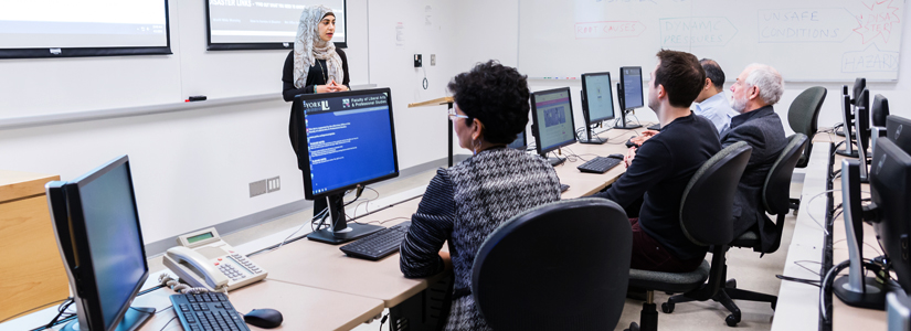 a student addressing a group of students sitting at computers